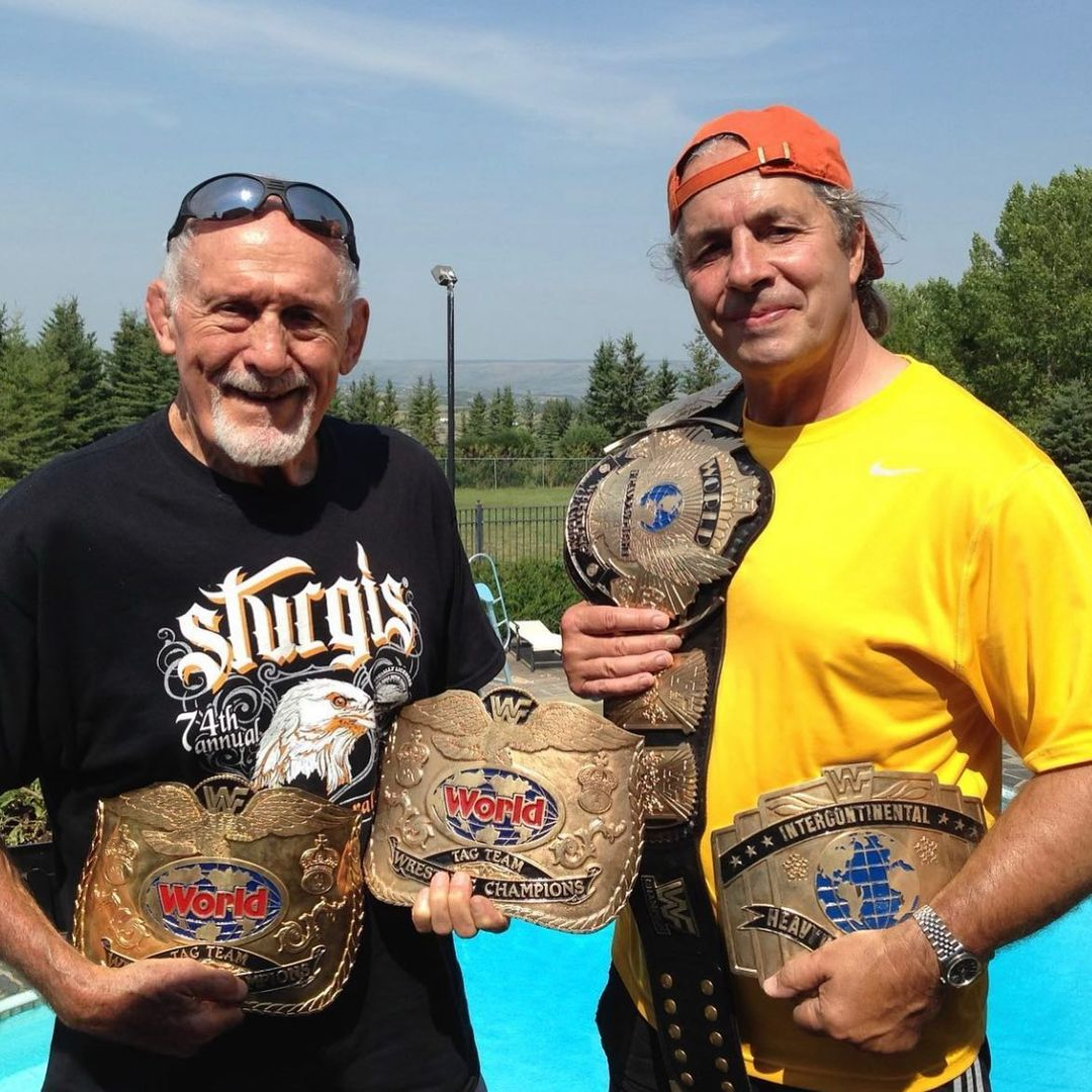 Reggie Parks with Bret Hart holding the WWF Championship Winged Eagle Intercontinental Championship Tag Team Championship Title Belts